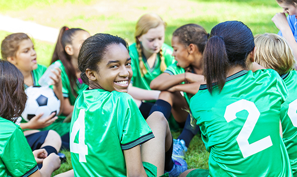 Beautiful African American girl turning around and smiling at camera while sitting down with her all girls soccer team. Their uniforms are a bright green.